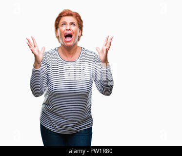 Atrractive senior caucasian redhead woman over isolated background crazy and mad shouting and yelling with aggressive expression and arms raised. Frus - Stock Photo