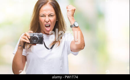 Middle age hispanic woman taking pictures using vintage photo camera over isolated background annoyed and frustrated shouting with anger, crazy and ye - Stock Photo