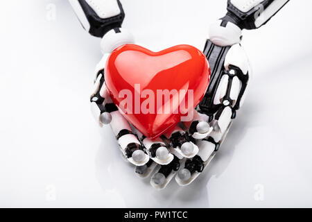 Elevated View Of Robotic Hand Holding Red Heart - Stock Photo