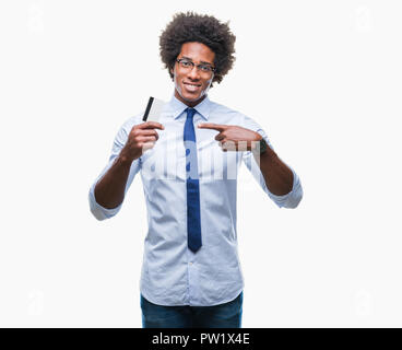 Afro american man holding credit card over isolated background very happy pointing with hand and finger - Stock Photo