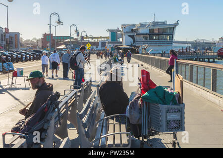 Two homeless men sit on the benches at Fisherman's Wharf, with tourists in background, San Francisco, California, United States. - Stock Photo