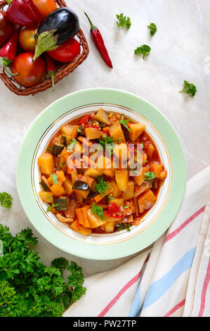 Delicious vegetable stew in a bowl on the table. Stewed potatoes, eggplants, zucchini, onions, carrots in spicy tomato sauce with greens. - Stock Photo