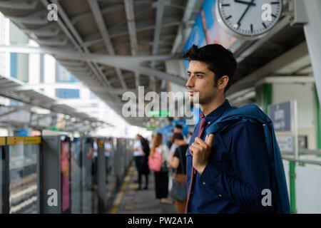 Young handsome Persian businessman exploring the city of Bangkok - Stock Photo