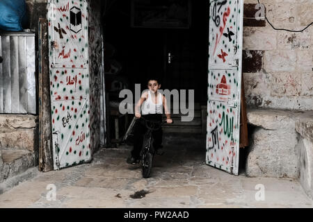 Jerusalem, Israel. 11th October, 2018. A young boy exits the African community residential area on a bicycle near the Chain Gate to Jerusalem's Temple Mount. The African Community Society is a non profitable Muslim NGO established by the African community members originally from Chad, Nigeria, Sudan and Suriname in Jerusalem in 1983. The society promotes culture in the Old City and empowers women and youth. - Stock Photo