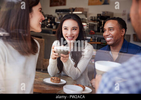 Four smiling friends having coffee at coffee shop, close up - Stock Photo