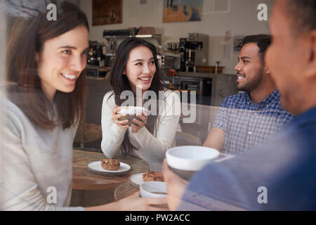 Four smiling adult friends sit having coffee at coffee shop - Stock Photo