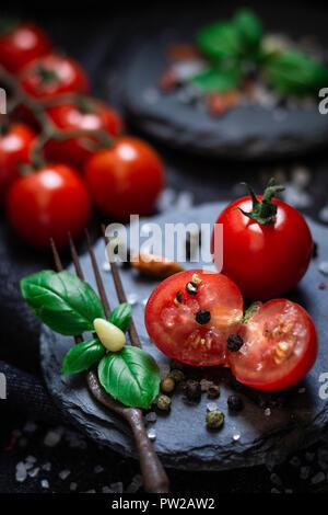 Frische Cherry Tomaten mit Basilikum auf Schiefer angerichtet - Stock Photo