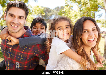 Young parents piggybacking their two kids outdoors - Stock Photo
