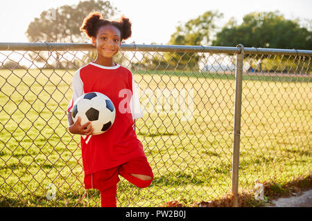 Pre teen black girl holding a soccer ball looking to camera - Stock Photo