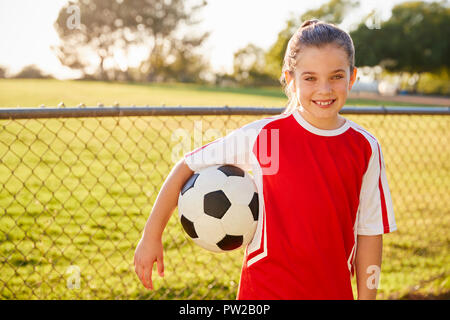 Schoolgirl in football strip holding ball, smiling to camera - Stock Photo