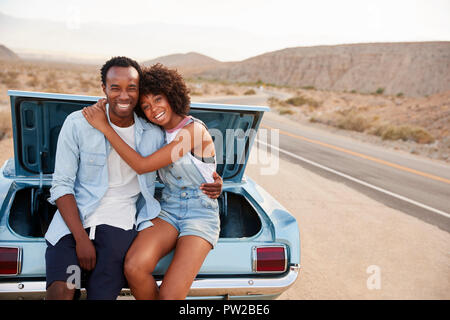 Portrait Of Couple Sitting In Trunk Of Classic Car On Road Trip - Stock Photo