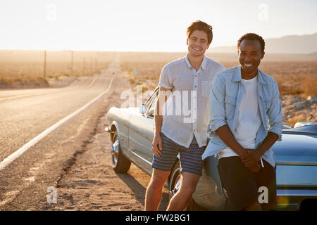 Portrait Of Two Male Friends Enjoying Road Trip Standing Next To Classic Car On Desert Highway - Stock Photo