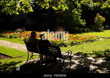 UK, Kent, Canterbury, Westgate Gardens, silhouetted senior couple sat in sunshine on bench amongst flowers - Stock Photo