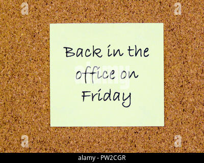 A yellow sticky note with back in the office on Friday written on it on a cork board background - Stock Photo