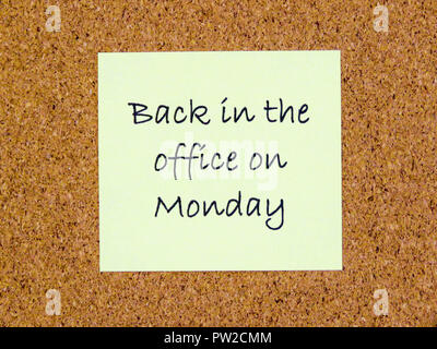 A yellow sticky note with back in the office on Monday written on it on a cork board background - Stock Photo