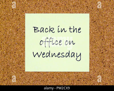 A yellow sticky note with back in the office on Wednesday written on it on a cork board background - Stock Photo