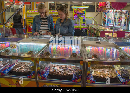 Two teenage girls playing on the slot machines inside an amusement arcade at Hayling Island, Hampshire, UK - Stock Photo