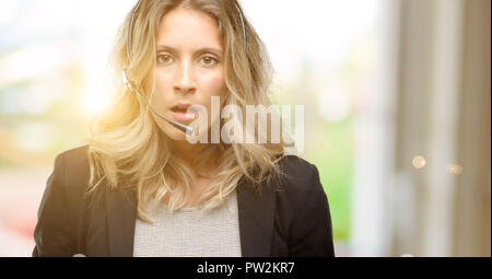 Young woman operator from call center scared in shock, expressing panic and fear - Stock Photo