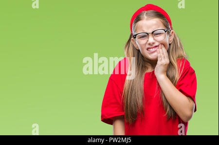 Young beautiful girl wearing glasses over isolated background touching mouth with hand with painful expression because of toothache or dental illness  - Stock Photo