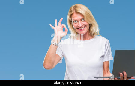 Middle age blonde woman using computer laptop over isolated background doing ok sign with fingers, excellent symbol - Stock Photo