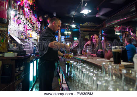 Bartender behind counter making cocktails in O'Donoghues Bar, Merrion Row, Dublin, Leinster, Ireland - Stock Photo