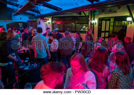 Men and women standing in covered courtyard outside O'Donoghues Bar, Merrion Row, Dublin, Leinster, Ireland - Stock Photo