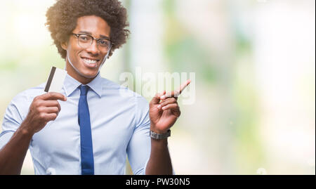 Afro american man holding credit card over isolated background very happy pointing with hand and finger to the side - Stock Photo