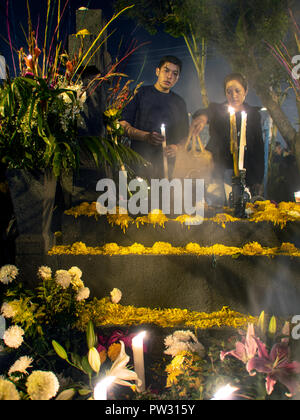 Men Remembering Loved Ones in the Historic Mixquic Cemetery in CDMX on the Day of the Dead - Stock Photo