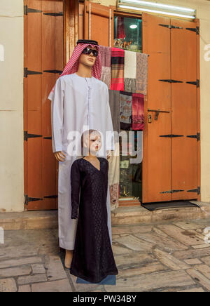 Traditional arabian clothing sold on the souk, Deira, Dubai, United Arab Emirates - Stock Photo