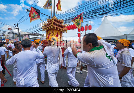 A street procession during the annual Vegetarian Festival in Phuket, Thailand, during which some participants pierce their bodies with strange objects - Stock Photo