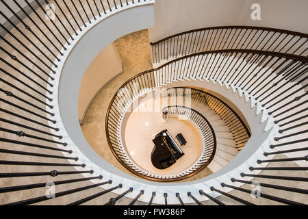 Interior shot of a spiral staircase with piano at the bottom - Stock Photo