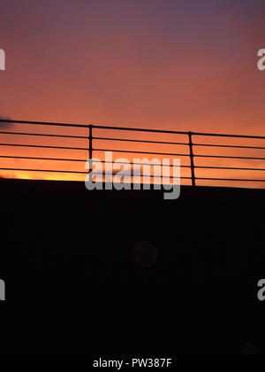 Silhouette of a Cruise Ship Railing against a Sunset Sky - Stock Photo