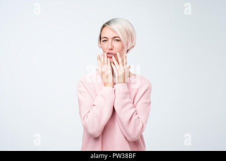 Young european woman look with disgust on her face on camera. It is stinking and she can not understand what. - Stock Photo