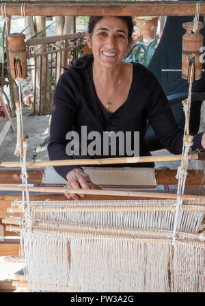 A woman using traditional weaving methods at a Museum in Fyti village, Cyprus. - Stock Photo