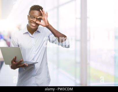 Young african american businessman using computer laptop with happy face smiling doing ok sign with hand on eye looking through fingers - Stock Photo
