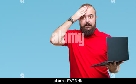 Young caucasian man using computer laptop over isolated background stressed with hand on head, shocked with shame and surprise face, angry and frustra - Stock Photo