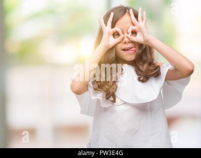 Brunette hispanic girl doing ok gesture like binoculars sticking tongue out, eyes looking through fingers. Crazy expression. - Stock Photo