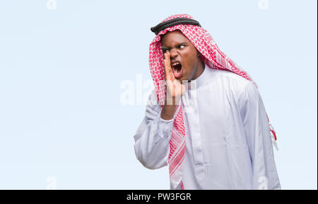 Young arabic african man wearing traditional keffiyeh over isolated background shouting and screaming loud to side with hand on mouth. Communication c - Stock Photo