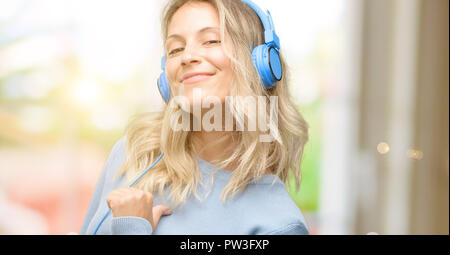 Young beautiful woman listening to music proud, excited and arrogant, pointing with victory face - Stock Photo