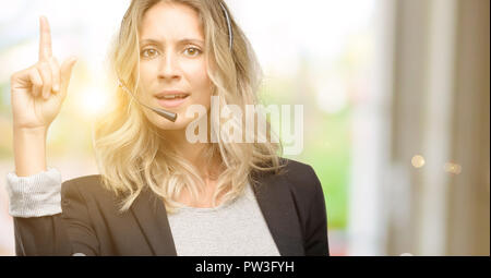 Young woman operator from call center happy and surprised cheering expressing wow gesture pointing up - Stock Photo