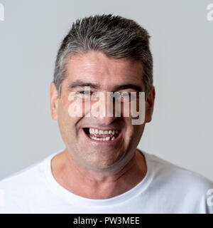 Close up portrait of an attractive middle aged man having fun and looking happy joyful smiling and laughing at the camera in human emotions facial exp - Stock Photo