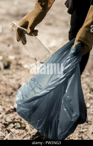 Man volunteering in forest wearing yellow gloves while gathering empty bottles - Stock Photo