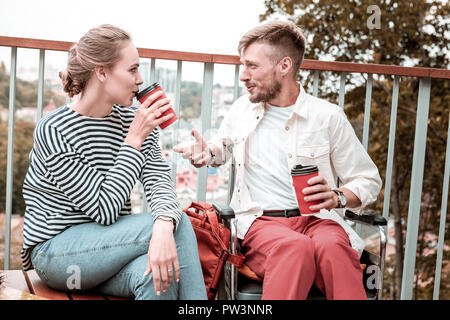 Two young friends drinking coffee and having nice conversation - Stock Photo