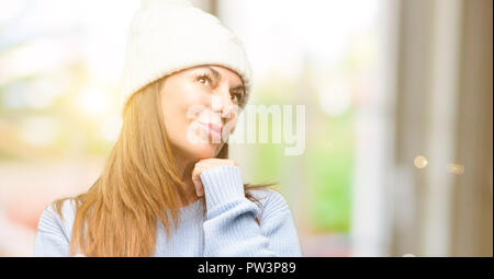Middle age woman wearing wool winter cap thinking and looking up expressing doubt and wonder - Stock Photo