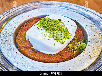 Kunefe, also known as Kenafeh, traditional Arab dessert made with Kadayif, a thin pastry noodle, soaked in syrup, layered with ice cream and pistachio - Stock Photo