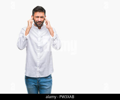 Adult hispanic man over isolated background covering ears with fingers with annoyed expression for the noise of loud music. Deaf concept. - Stock Photo