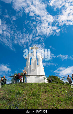 Vilnius Lithuania, view of tourists standing on the viewing terrace on Three Crosses Hill and looking down on the city of Vilnius below, Lithuania. - Stock Photo