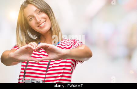 Young beautiful woman taking pictures using vintage photo camera over isolated background smiling in love showing heart symbol and shape with hands. R - Stock Photo