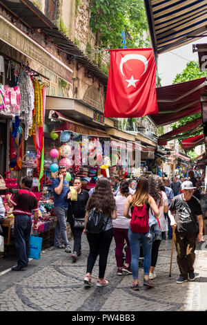 People walking down a narrow cobbled street past small shops with a large Turkish flag above, Istanbul, Turkey - Stock Photo