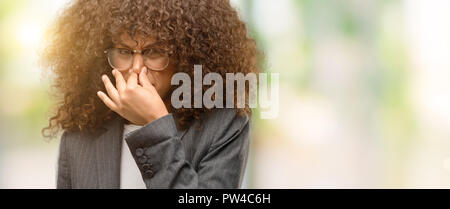 African american business woman wearing glasses smelling something stinky and disgusting, intolerable smell, holding breath with fingers on nose. Bad  - Stock Photo